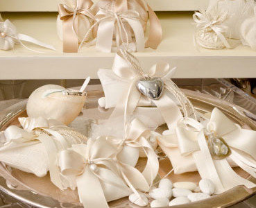 Silver tray. Favors made with linen bags, organza and silk containing sugared almonds and finished with satin ribbons and stylish décor.